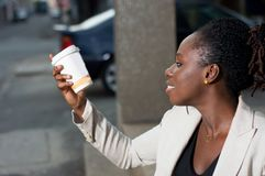 Jeune femme examinant un bol de café Image libre de droits