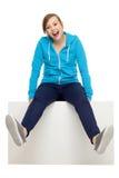 Jeune femme Excited s'asseyant sur quelque chose images stock