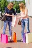 Jeune femme explorant leur panier sur la rue Photos stock