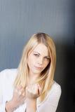 Jeune femme fâchée avec les poings serrés image stock