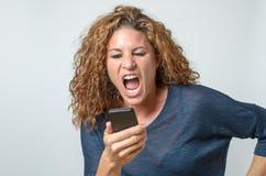 Jeune femme fâchée criant à son mobile Photographie stock libre de droits