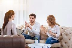 Jeune femme fâchée disant quelque chose à son mari image stock