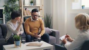 Jeune femme fâchée parlant au mari dans le bureau du psychothérapeute pendant la session banque de vidéos