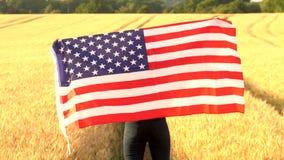 Jeune femme féminine d'adolescente de fille d'Afro-américain de métis tenant un drapeau américain de bannière étoilée des Etats-U banque de vidéos
