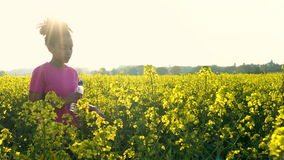 Jeune femme féminine d'adolescente de fille d'Afro-américain de métis courant buvant une bouteille de l'eau dans le domaine des f banque de vidéos
