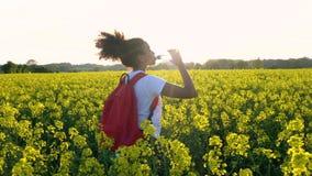 Jeune femme féminine d'adolescente de fille trimardant avec le sac à dos et la bouteille rouges de l'eau dans le domaine des fleu banque de vidéos
