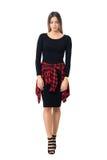 Jeune femme féminine triste dans la robe et le stylet noirs marchant et regardant vers le bas Photographie stock libre de droits