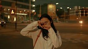 Jeune femme faisant à og de symbole de coeur ses doigts et cachant son joli visage devant la rue de ville de nuit avec defocused banque de vidéos