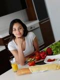 Jeune femme faisant cuire dans la cuisine Image libre de droits