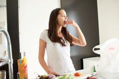 Jeune femme faisant cuire dans la cuisine Photographie stock libre de droits