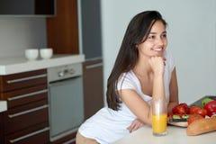 Jeune femme faisant cuire dans la cuisine Photo stock