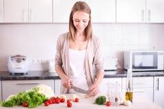 Jeune femme faisant cuire dans la cuisine Images libres de droits