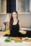 Jeune femme faisant cuire dans la cuisine Images stock