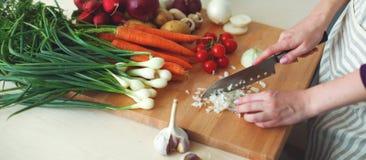 Jeune femme faisant cuire dans la cuisine Nourriture saine Images stock