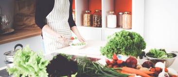 Jeune femme faisant cuire dans la cuisine Nourriture saine Photographie stock