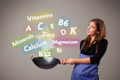 Jeune femme faisant cuire des vitamines et des minerais Photographie stock