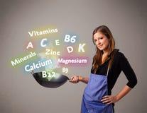 Jeune femme faisant cuire des vitamines et des minerais Photo stock