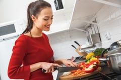 Jeune femme faisant cuire le dîner romantique à la maison coupant des légumes Photographie stock libre de droits