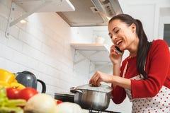Jeune femme faisant cuire le dîner romantique à la maison parlant utilisant le smartphone Photo stock