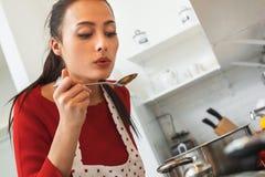 Jeune femme faisant cuire le dîner romantique à la maison refroidissant la soupe Images stock