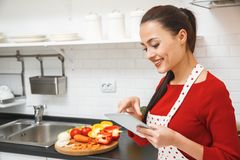 Jeune femme faisant cuire le dîner romantique à la maison se tenant utilisant le comprimé numérique images libres de droits