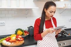 Jeune femme faisant cuire le dîner romantique à la maison tenant le comprimé numérique de lecture rapide Photos stock