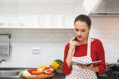 Jeune femme faisant cuire le dîner romantique à la maison vérifiant des ingrédients Image libre de droits