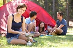 Jeune femme faisant cuire le petit déjeuner pour des amis des vacances de camping Images libres de droits