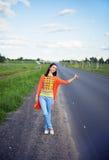 Jeune femme faisant de l'auto-stop Image stock