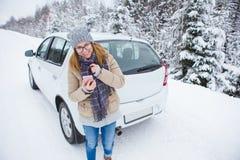 Jeune femme faisant de l'auto-stop sur la route couverte de neige d'hiver photo stock