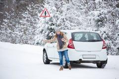 Jeune femme faisant de l'auto-stop sur la route couverte de neige d'hiver Image libre de droits