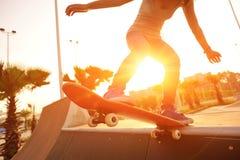 Jeune femme faisant de la planche à roulettes au lever de soleil Images libres de droits