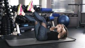 Jeune femme faisant des augmenter de jambe dans un gymnase banque de vidéos