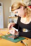 Jeune femme faisant des bijoux à la maison photos stock