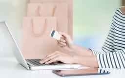 Jeune femme faisant des emplettes en ligne avec le débit/carte de crédit, le paiement et le concept de vente image stock