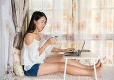 Jeune femme faisant des emplettes en ligne par la fenêtre Images libres de droits