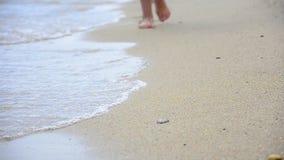 Jeune femme faisant des empreintes de pas au sable de plage banque de vidéos