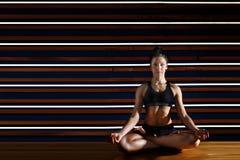 Jeune femme faisant des exercices de yoga dans le studio foncé Concept de mode de vie de santé Photo stock