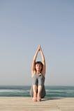 Jeune femme faisant des exercices sur la plage Photographie stock libre de droits
