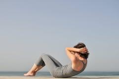 Jeune femme faisant des exercices sur la plage Photographie stock