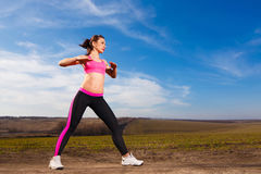 Jeune femme faisant des exercices sur le fond de ciel bleu Photos stock