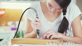 Jeune femme faisant des utilisations faites main de bijoux et de graveur pour les perles en verre banque de vidéos