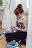 Jeune femme faisant du crochet avec le fil sur le plancher Photographie stock libre de droits