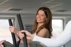 Jeune femme faisant l'aérobic Walker In Gym elliptique image stock