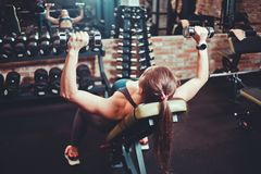 Jeune femme faisant l'exercice avec des haltères pour les muscles photographie stock