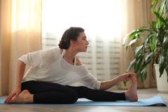 Jeune femme faisant l'exercice de détente méditant de yoga à la maison Style de vie sain méditation de pratique femelle sur le pl Image libre de droits