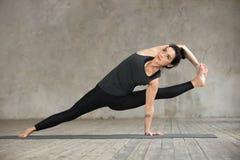 Jeune femme faisant l'exercice de Visvamitrasana images stock