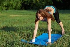 Jeune femme faisant l'exercice de yoga sur le parc Photos libres de droits