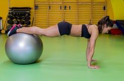 Jeune femme faisant l'exercice sur la boule de forme physique photos stock