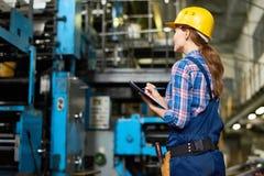 Jeune femme faisant l'inventaire à l'usine moderne images stock